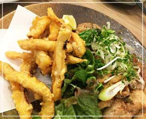 「日本酒原価酒蔵」にて、日本酒にぴったりな塩味のイカ天ぷらと、山椒の利いた鶏のグリル。