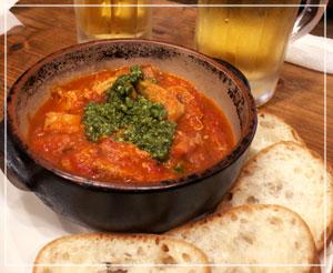 ざくざくたっぷりトリッパが入るトマト煮込み。バジル風味のソースとバゲットつきで。